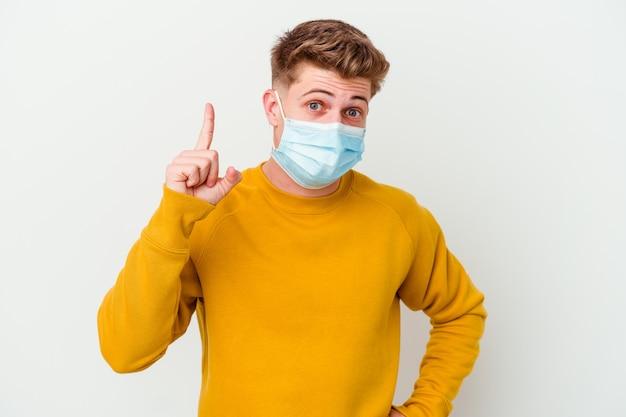 Giovane che indossa una maschera per il coronavirus isolato su sfondo bianco con un'idea, un concetto di ispirazione.