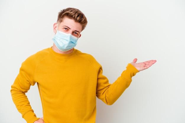 Giovane che indossa una maschera per il coronavirus isolato su sfondo bianco che mostra uno spazio di copia su un palmo e tiene un'altra mano sulla vita.