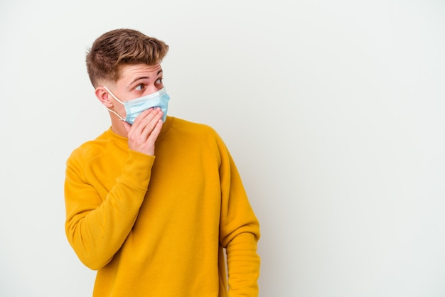 Giovane che indossa una maschera per il coronavirus isolato su sfondo bianco premuroso guardando uno spazio di copia che copre la bocca con la mano.