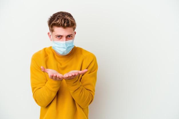 Giovane che indossa una maschera per il coronavirus isolata sul muro bianco, piegando le labbra e tenendo i palmi delle mani per inviare un bacio d'aria.