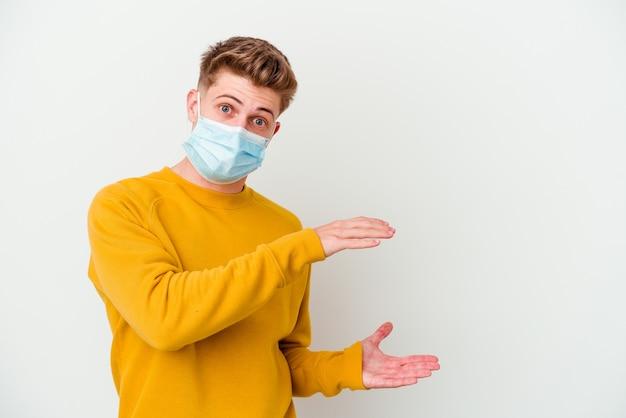 Giovane che indossa una maschera per il coronavirus isolata sul muro bianco scioccato e stupito tenendo una copia spazio tra le mani.