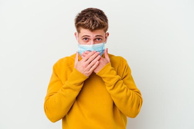 Giovane che indossa una maschera per il coronavirus isolato sul muro bianco scioccato che copre la bocca con le mani.