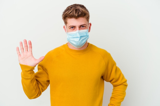 Giovane che indossa una maschera per il coronavirus isolato sul muro bianco sorridente allegro che mostra il numero cinque con le dita.
