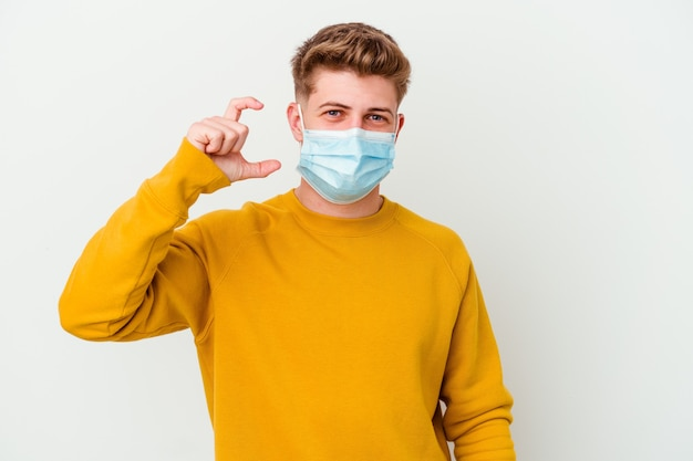 Giovane che indossa una maschera per il coronavirus su bianco che tiene qualcosa di piccolo con gli indici, sorridente e sicuro di sé.