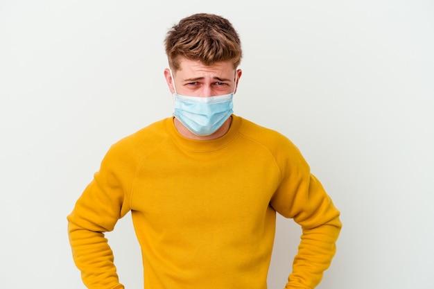 Giovane che indossa una maschera per il coronavirus su bianco che urla molto arrabbiato e aggressivo.