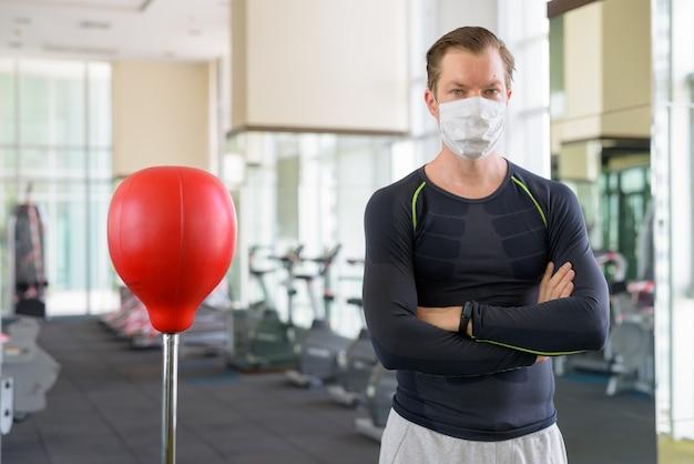 Giovane uomo che indossa la maschera con le braccia incrociate pronto per la boxe in palestra durante il coronavirus covid-19