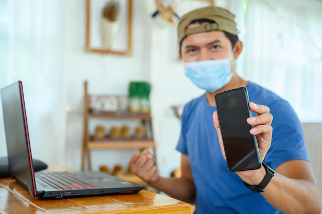 Il giovane che indossa una maschera lavora online con successo mostra il telefono cellulare con lo schermo vuoto uomo asiatico che lavora da casa