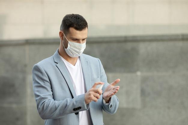 Giovane uomo che indossa la maschera medica utilizzando gel disinfettante per le mani a piedi in città