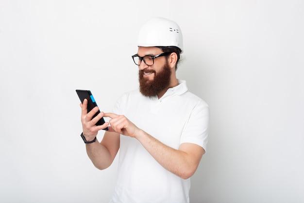 Il giovane che indossa un elmetto di protezione sta guardando il suo tablet.