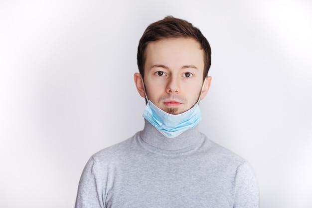 Giovane uomo che indossa una maschera protettiva contro il virus corona covid 19. uomo bruno che indossa una maschera chirurgica per prevenire il virus