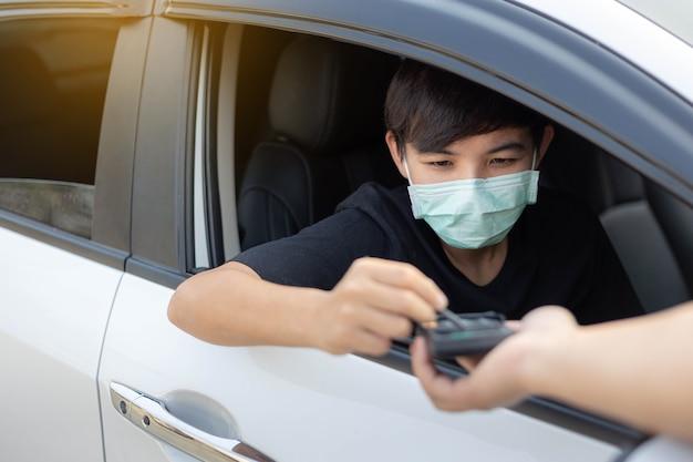 Un giovane che indossava una maschera protettiva ha usato la carta di credito per il pagamento al servizio di ristorazione drive thru. focolaio covid-19, concetto medico, sanitario e di quarantena.