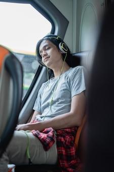 Un giovane che indossa le cuffie per dormire mentre ascolta la musica mentre è seduto vicino alla finestra durante un viaggio in autobus