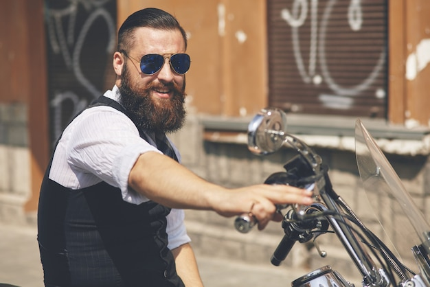 Giovane uomo che indossa occhiali da sole e seduto su una moto