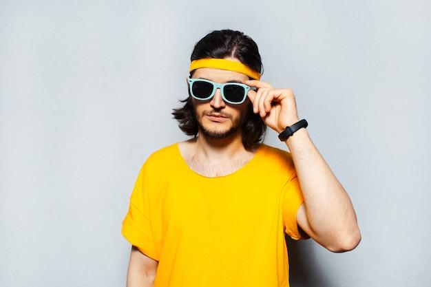Giovane uomo che indossa occhiali da sole e maglietta gialla su sfondo grigio.