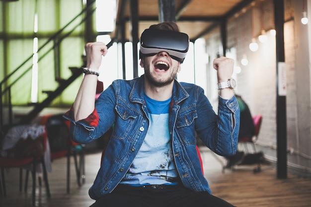 Giovane uomo che indossa occhiali per realtà virtuale in un moderno studio di coworking di interior design. smartphone utilizzando con auricolare occhiali vr.
