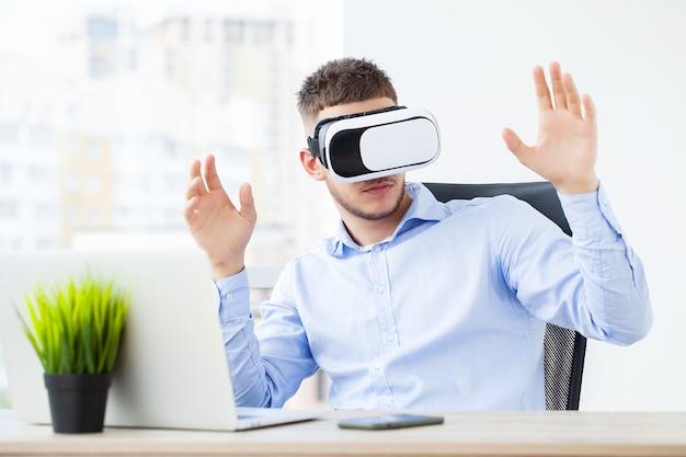 Giovane uomo che indossa occhiali per realtà virtuale in un ufficio moderno.