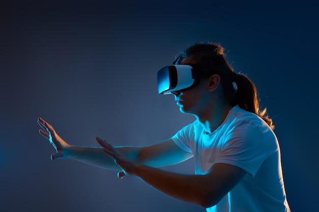Giovane uomo che indossa occhiali per realtà virtuale su sfondo blu scuro. luce al neon.