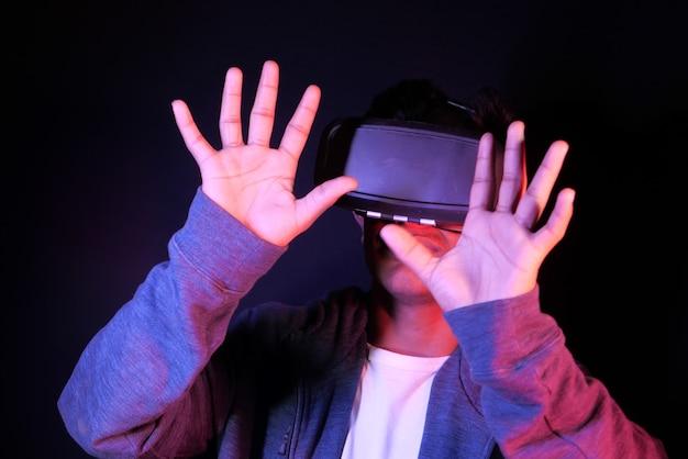 Giovane uomo che indossa la realtà virtuale auricolare vr box isolato su bianco