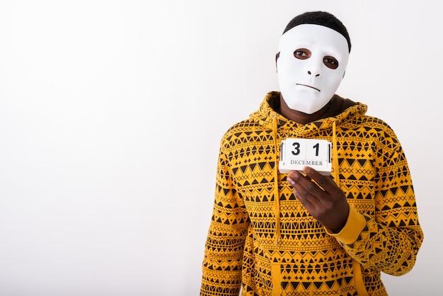 Giovane uomo che indossa una maschera bianca mentre si tiene il calendario