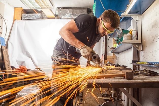 Un giovane saldatore con una maglietta nera, occhiali e guanti da costruzione smerigliatrice in metallo una smerigliatrice angolare in garage