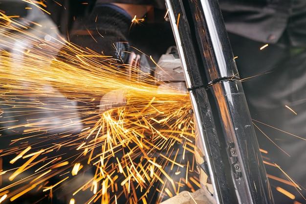 Un giovane uomo saldatore smerigliatrice auto in metallo una smerigliatrice angolare in officina, scintille volano al lato