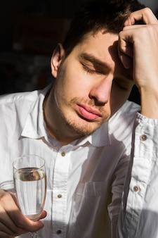 Giovane in camicia bianca con bicchiere in mano. uomo triste con alcool. alcolismo