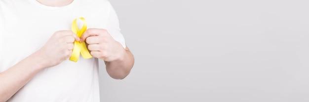 Giovane in maglietta bianca che tiene il simbolo di consapevolezza del nastro giallo per il suicidio