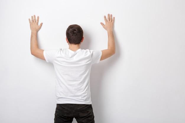 Giovane in maglietta bianca con le mani in alto vicino al muro bianco, vista posteriore. detenuto