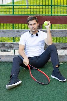 Giovane uomo in maglietta bianca con racchetta da tennis sul campo di calcio artificiale