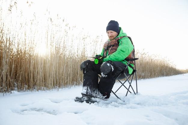 Un giovane uomo su un pescatore invernale si siede su una sedia e pesci e una canna da pesca