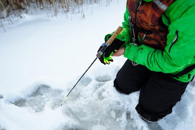 Giovane uomo su una battuta di pesca invernale su un lago innevato pesci su una canna da pesca