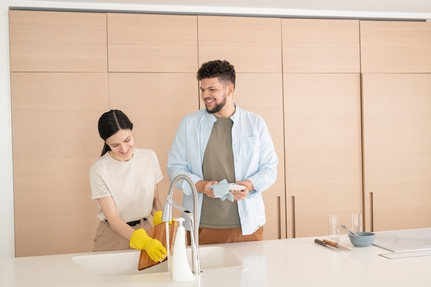 Giovane che pulisce i piatti lavati dalla moglie in cucina