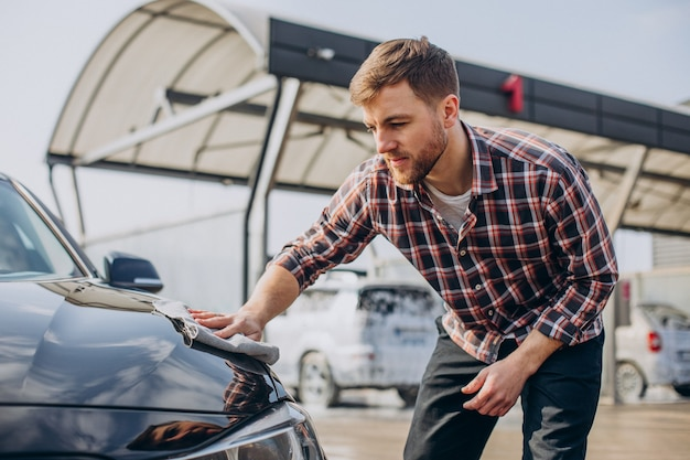 Giovane che pulisce la sua auto dopo l'autolavaggio