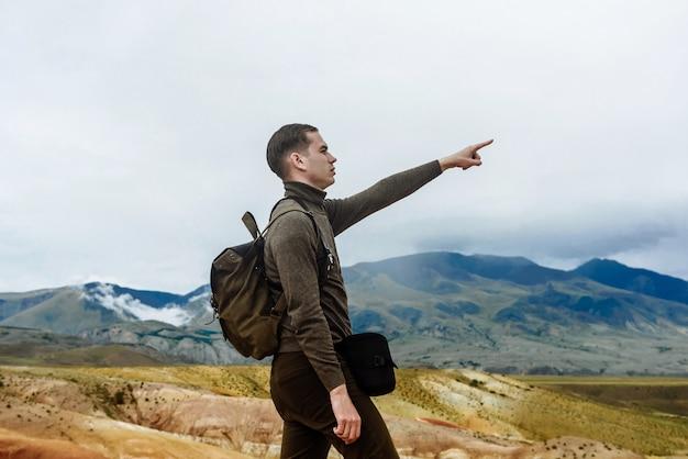 Il giovane con uno zaino con una mano alzata indica la distanza