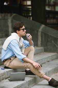 Giovane con cattive abitudini. giovani fumatori moderni. stile di vita malsano, uomo d'affari in pausa caffè su sfondo urbano