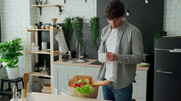 Un giovane con un sacco di generi alimentari controlla ed esamina la ricevuta di un prodotto dopo aver acquistato cibo in un negozio di alimentari