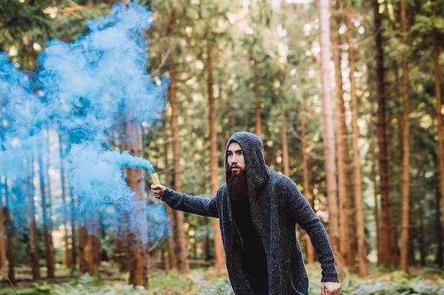 Il giovane con la barba nella foresta tiene il fumo blu