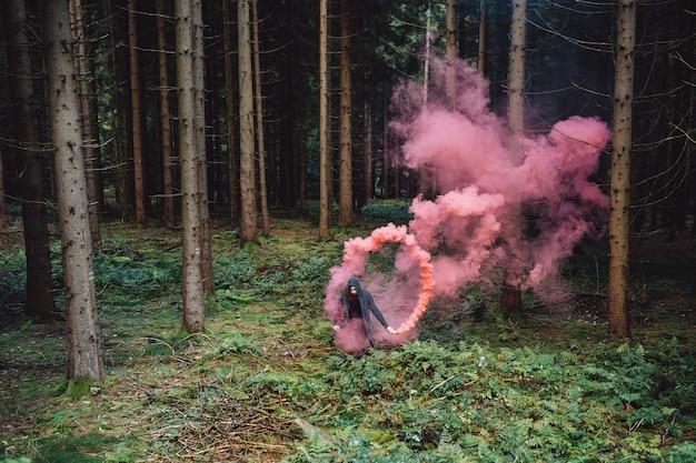 Il giovane con la barba nella foresta tiene il fumo colorato