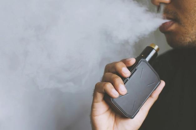Giovane con la barba in attesa e fumando la sua sigaretta elettronica soffiando un flusso di fumo diffuso.