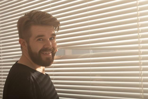 Giovane uomo con la barba fa capolino attraverso il foro nelle persiane della finestra e guarda fuori in strada