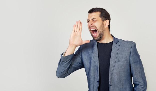 Un giovane con la barba urla ad alta voce con la mano vicino alla bocca