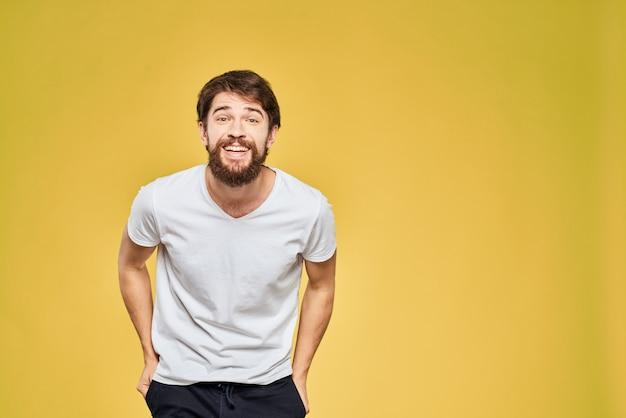 Un giovane con la barba in maglietta mostra emozioni diverse, divertimento, tristezza, rabbia