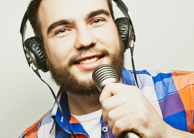 Un giovane con la barba che indossa una maglietta con in mano un microfono e canta, stile hipster