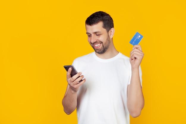 Giovane con la barba in una maglietta bianca che tiene una carta di credito.