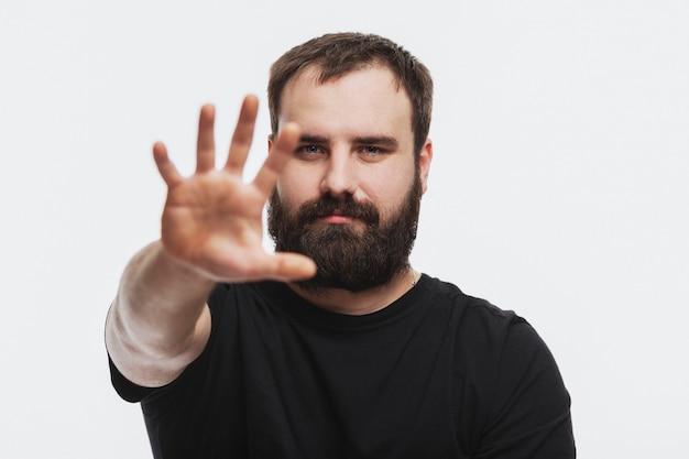 Un giovane con la barba con la mano tesa in avanti. nessun segno. sfondo bianco.