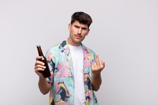 Giovane con una birra che si sente arrabbiato, infastidito, ribelle e aggressivo, ribaltando il dito medio per rispondere