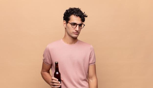 Giovane con una birra che si sente triste, arrabbiato o arrabbiato e guarda di lato con un atteggiamento negativo, accigliato in disaccordo