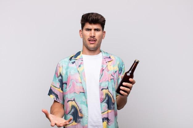 Giovane con una birra che sembra arrabbiato, infastidito e frustrato urlando wtf o cosa c'è di sbagliato in te