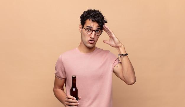 Giovane con una birra che sembra felice, stupito e sorpreso, sorridente e realizzando incredibili e incredibili buone notizie