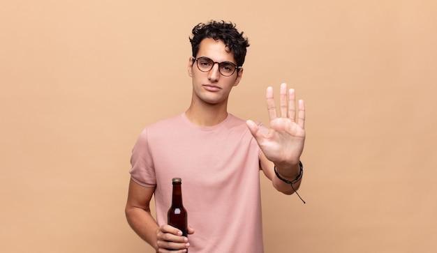 Giovane con una birra che sembra serio, severo, dispiaciuto e arrabbiato che mostra il palmo aperto che fa il gesto di arresto
